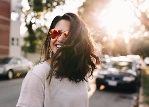 A girl smiling wearing sunglasses